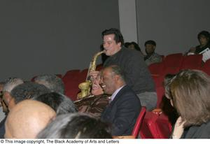 Primary view of object titled '[Man playing a saxophone for audience members]'.