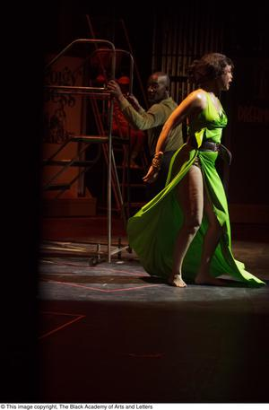 Primary view of object titled '[Performer in green dress in spotlight]'.