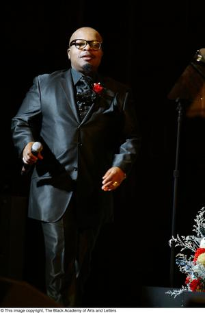 Primary view of object titled '[Performer in black suit walking on stage]'.