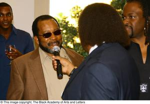 Primary view of object titled '[Curtis King holding microphone for guest]'.