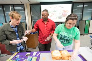 Color photograph of three people working on building a cake. Boxes of food and various supplies sit on the table.