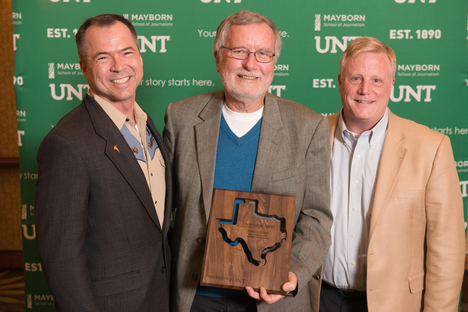 """[David Collins holding trophy with guests at Literary Lights Dinner], Photograph of David Collins standing with two guests in front of a UNT and Mayborn backdrop. He is holding the first place plaque for the Literary Excellence award, which he received for his book manuscript """"Accidental Texas Activists: Mark Phariss, Vic Holmes, and their Fight for Marriage Equality in the Lone Star State"""". The win granted him a provisional book contract with UNT Press and it was awarded to him at the Literary Lights Dinner during the Mayborn Literary Nonfiction Conference. The dinner was held in the International Ballroom at the Hilton DFW Lakes Executive Conference Center, Grapevine, TX.,"""