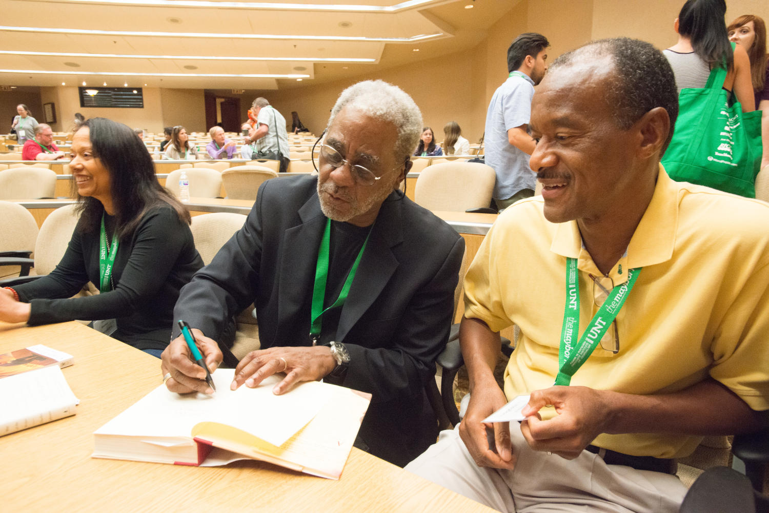 [Charles Johnson signing book], Photograph of Dr. Charles Johnson, a professor emeritus at the University of Washington and author, signing a keynote attendees copy of one of his books. He is sitting down at one of the tables in the conference and auditorium room where his keynote was given. Jesika Fisher is standing behind him with other attendees. The event was a part of the 2017 Mayborn Literary Nonfiction Conference at the Hilton DFW Lakes Executive Conference in Grapevine, TX.,