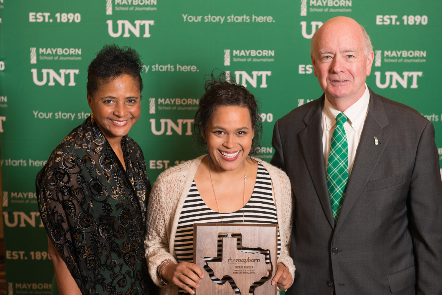 """[Kerri Fischer standing with Dorothy Bland and Joe Dealy Jr.], Photograph of (L-R) Dorothy Bland, Kerri Fischer, and Joe Dealy Jr. standing in front of a UNT and Mayborn backdrop. Fischer is holding the Third Place Literary Excellence award from The Mayborn for her book manuscript, """"Black, White, Other: Stories of Race, Wonder and Self-Integration"""". The award was presented to her at the Literary Lights Dinner during the Mayborn Literary Nonfiction Conference. The dinner was held in the International Ballroom at the Hilton DFW Lakes Executive Conference Center, Grapevine, TX.,"""
