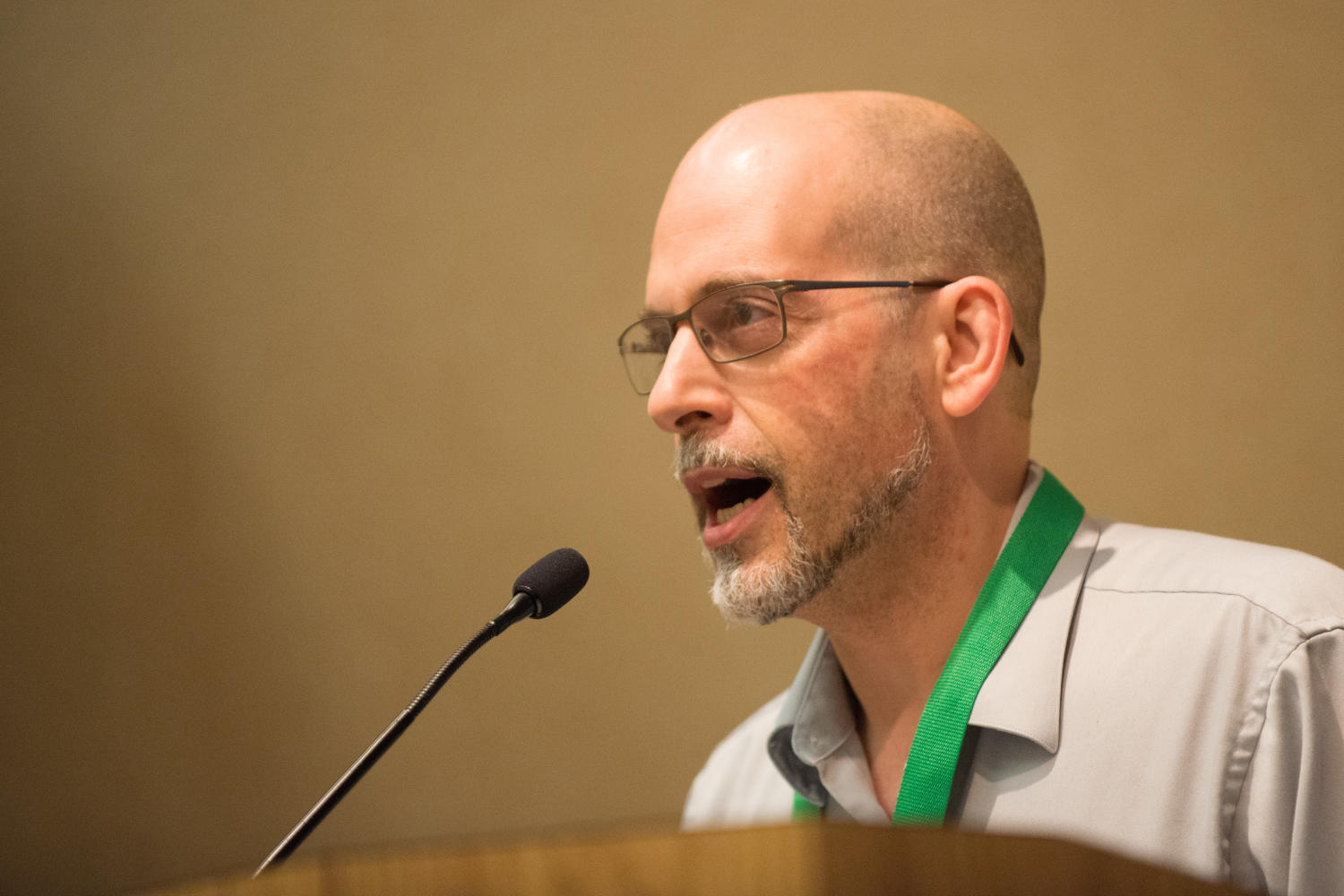 """[Mark Johnson speaking at a plenary titled """"Deconstruction of a Deadline Narrative""""], Photograph of Mark Johnson standing at a podium and speaking during the plenary called """"Deconstruction of a Deadline Narrative"""". The event was held as a part of the Mayborn Literary Nonfiction Conference at the Hilton DFW Lakes Executive Conference Center in Grapevine, Texas.,"""