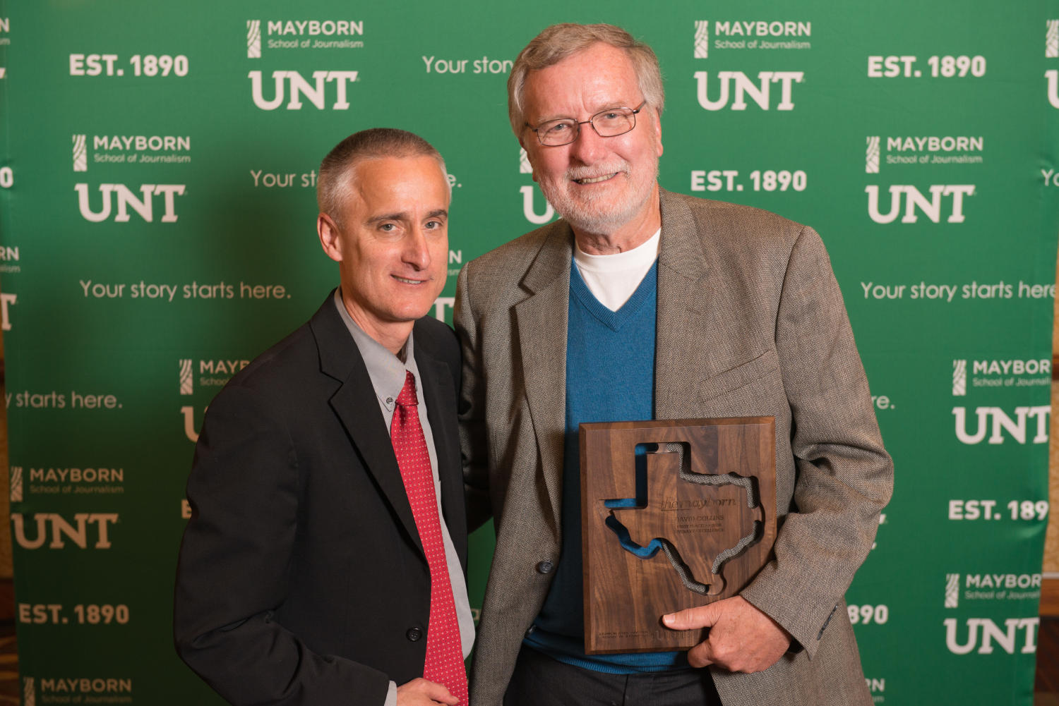 """[David Collins standing with guest and holding award], Photograph of David Collins standing with a guest in front of a UNT and Mayborn backdrop. He is holding the first place plaque for the Literary Excellence award, which he received for his book manuscript """"Accidental Texas Activists: Mark Phariss, Vic Holmes, and their Fight for Marriage Equality in the Lone Star State"""". The win granted him a provisional book contract with UNT Press and it was awarded to him at the Literary Lights Dinner during the Mayborn Literary Nonfiction Conference. The dinner was held in the International Ballroom at the Hilton DFW Lakes Executive Conference Center, Grapevine, TX.,"""