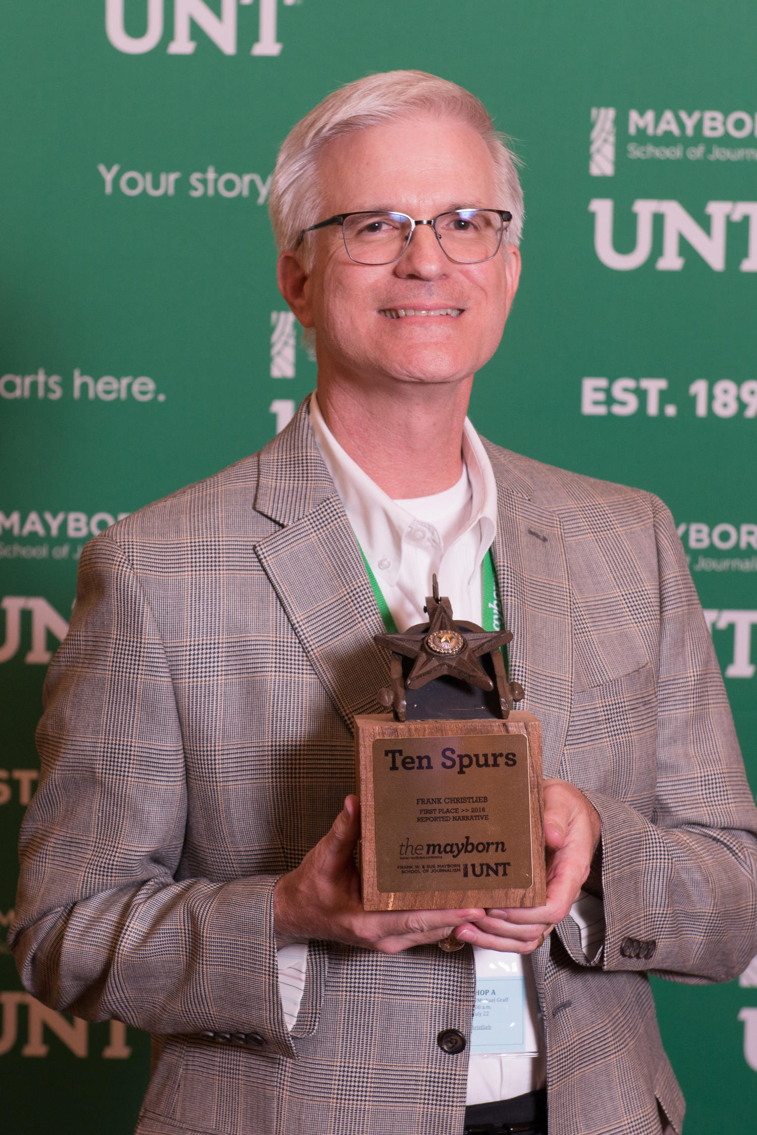 [Frank Christlieb holding first place Ten Spurs trophy], Photograph of Frank Christlieb, a writer and editor with The Dallas Morning News, holding his Ten Spurs third place award for Reported Narrative. He received the honor at the Literary Lights Dinner during the Mayborn Literary Nonfiction Conference. The dinner was held in the International Ballroom at the Hilton DFW Lakes Executive Conference Center, Grapevine, TX.,