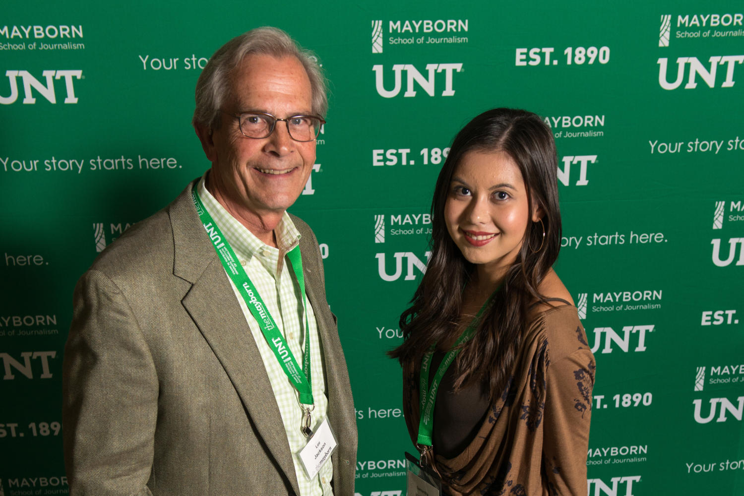 """[Chancellor Lee Jackson and Samantha McDonald], Photograph of UNT System Chancellor Lee Jackson standing with Samantha McDonald, a winner of the Minority College Student Award, in front of a backdrop detailed with Mayborn and UNT logos and the tagline """"Your story starts here."""" They are being photographed at the Austin Ranch Banquet Hall during the Mayborn Literary Nonfiction Conference on the grounds of the Hilton DFW Lakes Executive Conference Center in Grapevine, Texas.,"""