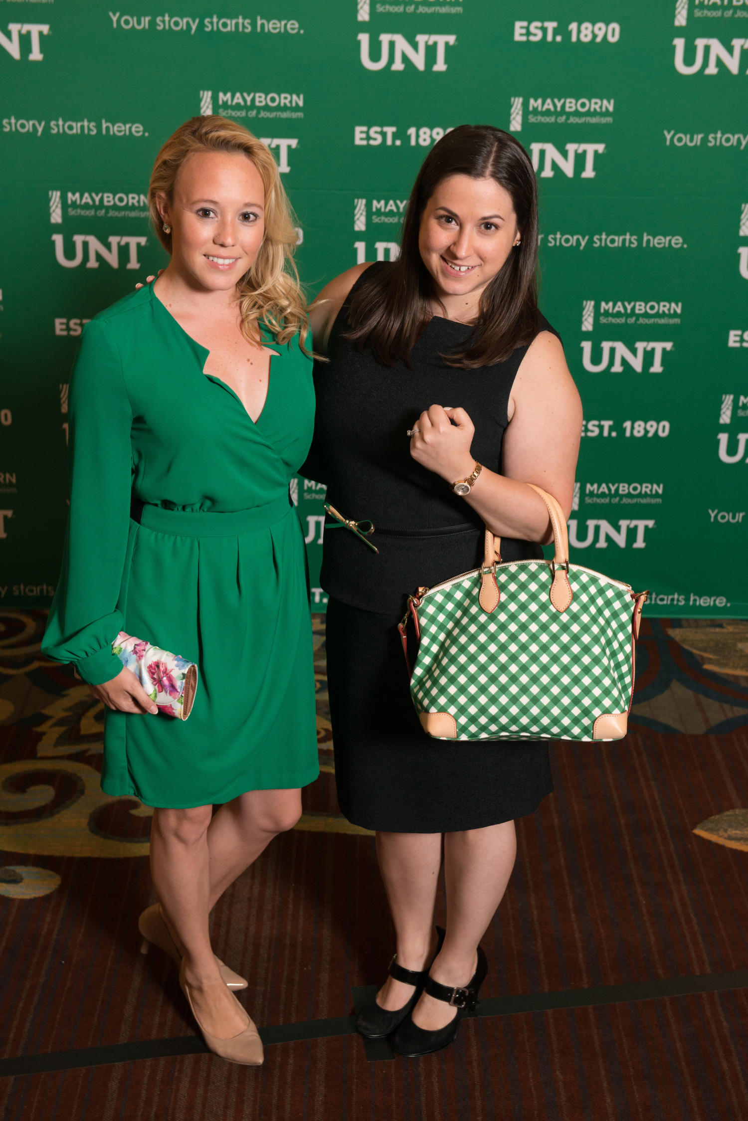 [Two women standing together at Literary Lights Dinner], Photograph of two women standing together in front of a Mayborn and UNT backdrop during the Literary Lights Dinner. The event was held as a part of the Mayborn Literary Nonfiction Conference in the International Ballroom at the Hilton DFW Lakes Executive Conference Center, Grapevine, TX.,