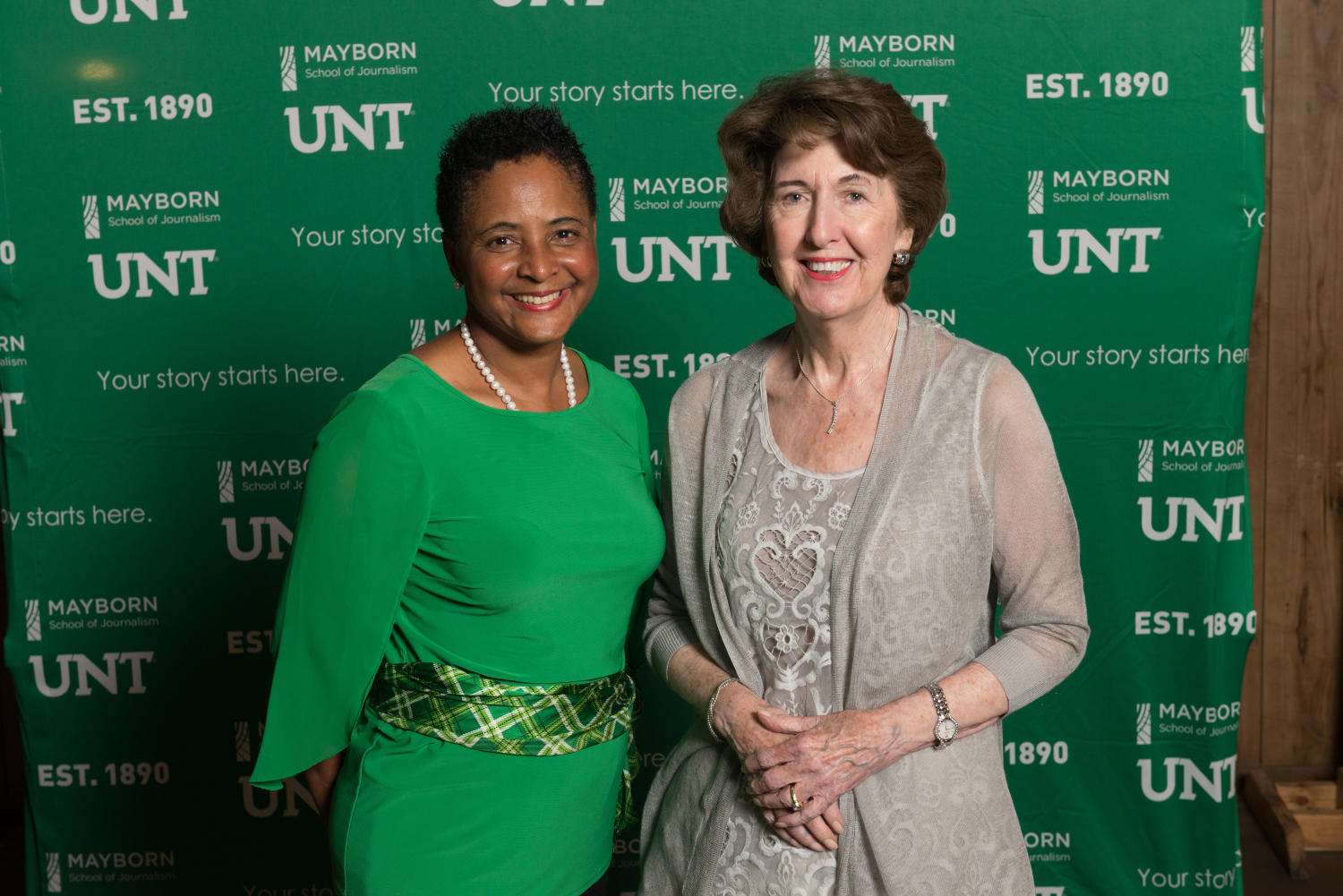 """[Dorothy Bland and Sue Mayborn in front of backdrop], Photograph of Dorothy Bland, the dean of the Mayborn School of Journalism, and Sue Mayborn, the president of the Frank and Sue Mayborn Foundation, standing together in front of a UNT and Mayborn labeled backdrop. The phrase """"Your story starts here"""" is on it too. Both are attending the Mayborn Literary Nonfiction Conference at the Hilton DFW Lakes Executive Conference Center in Grapevine, TX.,"""