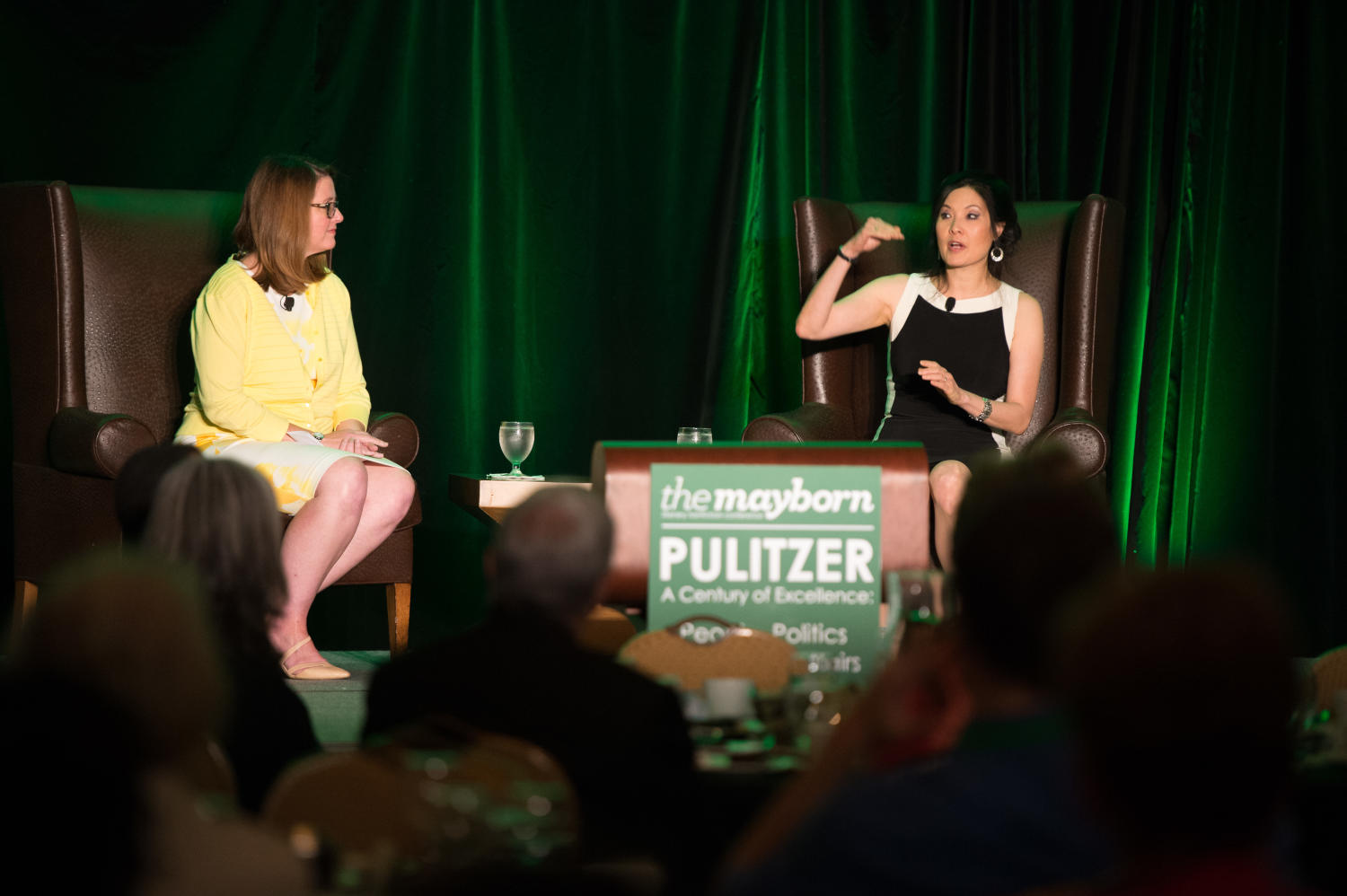 [Krys Boyd and Sheryl WuDunn sitting on stage during Literary Lights Dinner], Photograph of Krys Boyd (yellow) and Sheryl WuDunn (black), the first Asian American reporter to win a Pulitzer Prize, sitting on stage at the Literary Lights Dinner. WuDunn is speaking to those it attendance and is also gesturing with her hands. She was invited to be the Keynote Speaker at the event held by the Mayborn Literary Nonfiction Conference. There is a screen next to them that is displaying an enlarged image of the two sitting down. The dinner took place in the International Ballroom at the Hilton DFW Lakes Executive Conference Center, Grapevine, TX.,