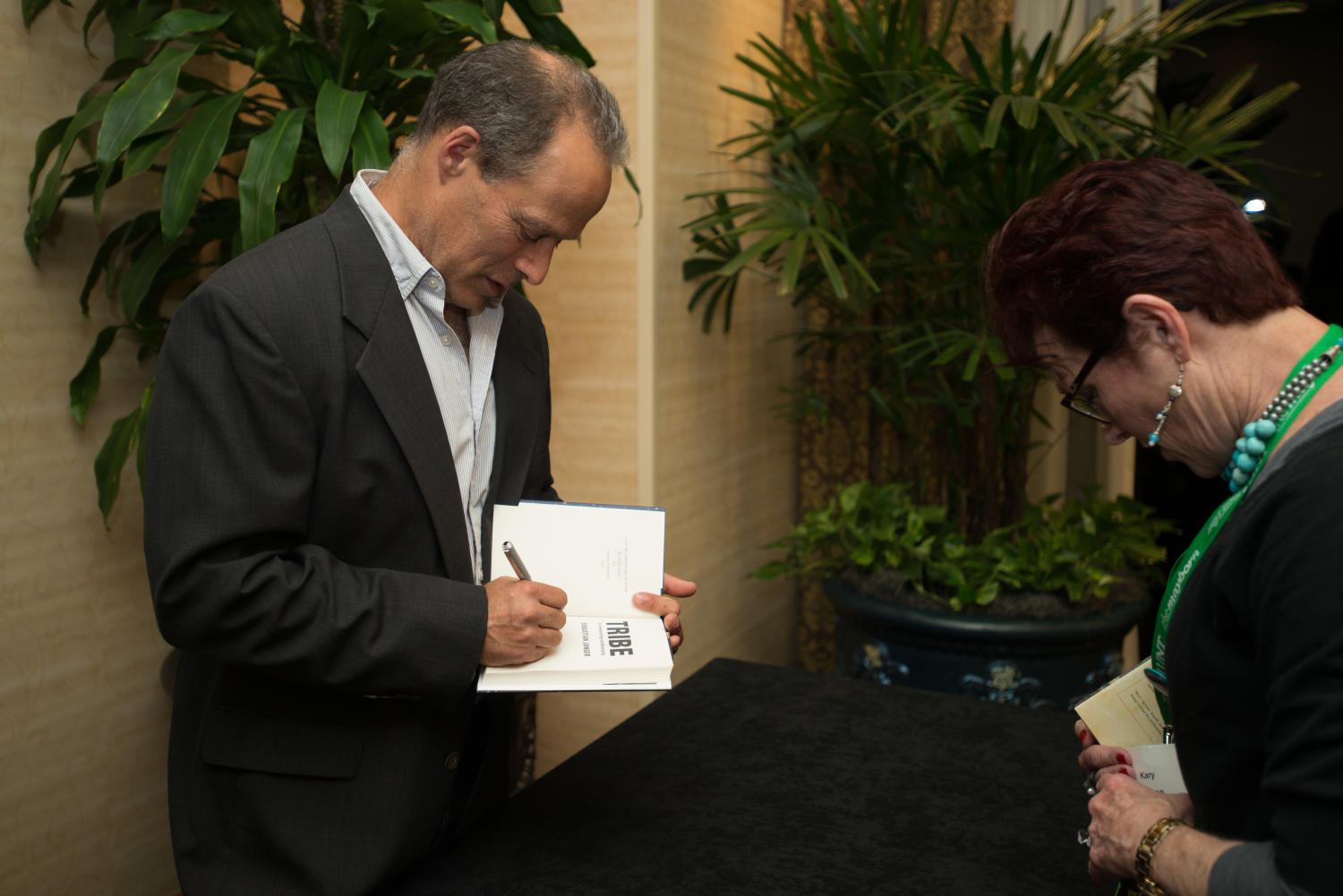 """[Sebastian Junger signing his book], Photograph of Sebastian Junger, author of the book """"Tribe"""", signing a copy of his book for a conference attendee with the first name Kary. They are standing at a table set up against one of the walls outside of the dining area. The signing was a part of the 2017 Mayborn Literary Nonfiction Conference, which was held at the Hilton DFW Lakes Executive Conference Center in Grapevine, TX.,"""