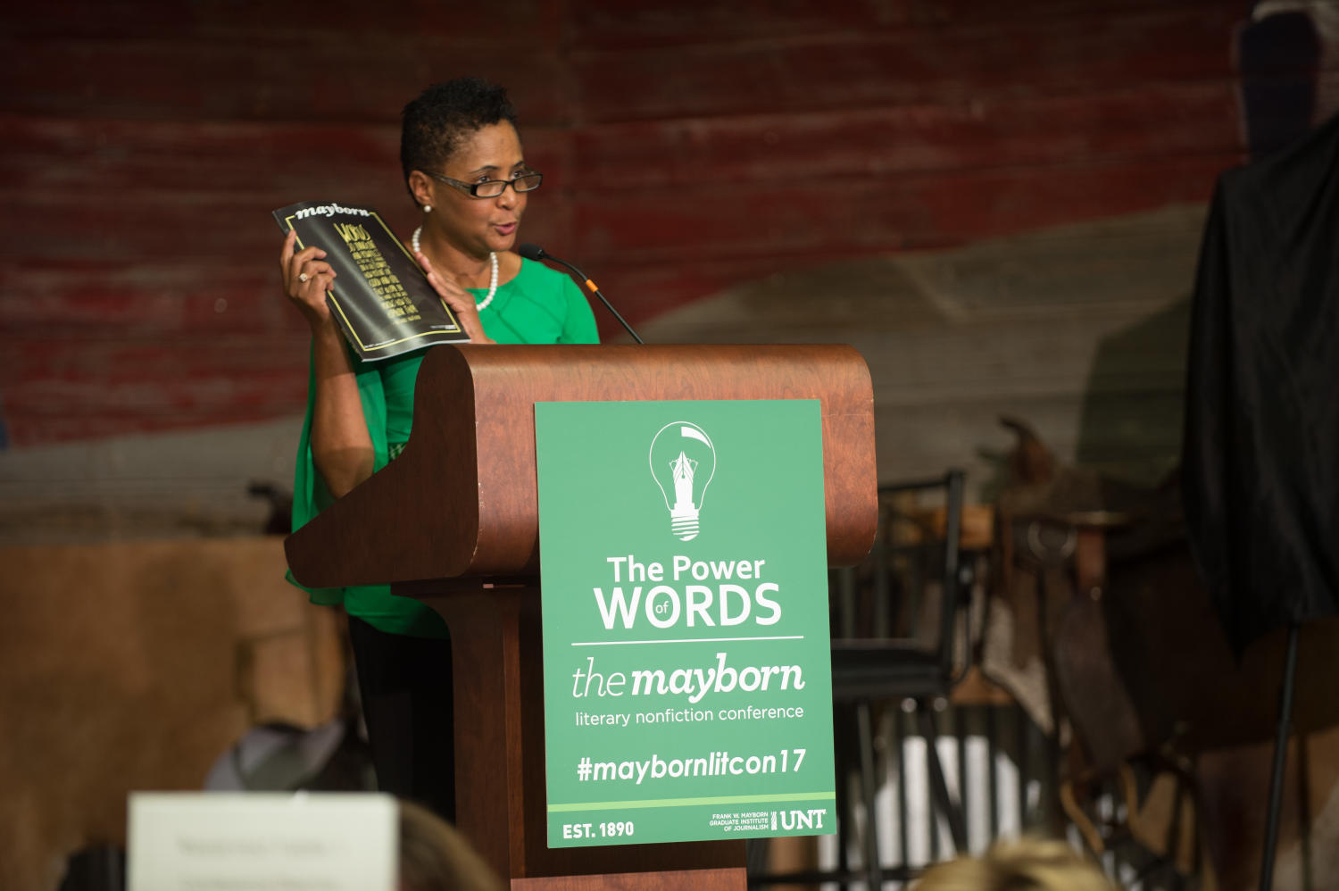"""[Dorothy Bland speaking from podium], Photograph of Dorothy Bland, dean of the Mayborn School of Journalism, speaking to the attendees of the Mayborn Literary Nonfiction Conference from behind a podium. She is holding up the magazine that was published for the event and the poster on the front of the podium reads """"The Power of Words, The Mayborn Literary Nonfiction Conference, #maybornlitcon17"""". They are all gathered in the Austin Ranch Banquet Hall on the grounds of the Hilton DFW Lakes Executive Conference Center in Grapevine, TX.,"""