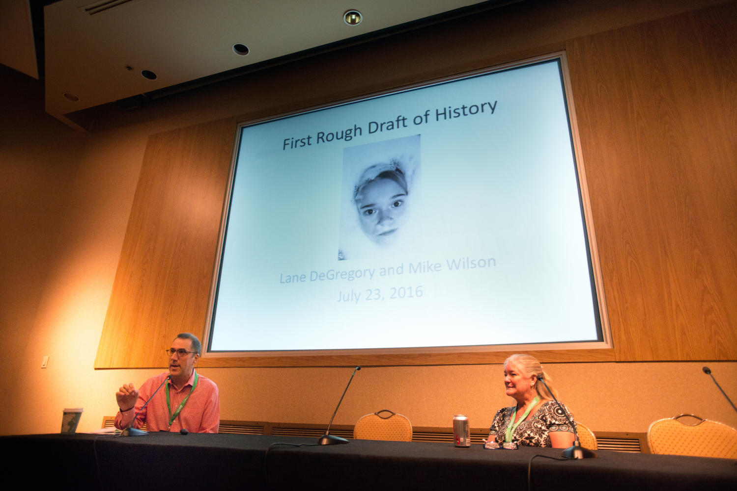 """[Mike Wilson and Lane DeGregory sitting at panelist table], Photograph of Mike Wilson and Lane DeGregory sitting down at the """"First Rough Draft of History"""" panelist table in a conference room. Behind them is a screen that reads """"First Rough Draft of History"""", underneath that is a photo of a face surrounded by bubbles, followed by the words """"Lane DeGregory and Mike Wilson July 23, 2016"""". The panel was held as a part of the Mayborn Literary Nonfiction Conference at the Hilton DFW Lakes Executive Conference Center, Grapevine, TX.,"""
