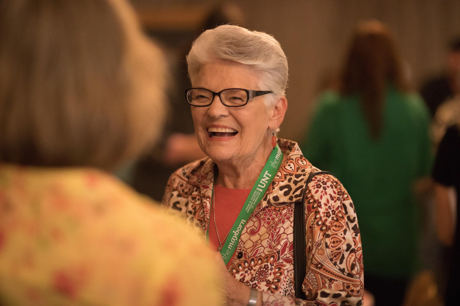 [Attendee laughing during conversation], Photograph of an attendee of the Mayborn Literary Nonfiction Conference laughing while having a conversation with others. They are gathered in the Austin Ranch Banquet Hall at the Hilton DFW Lakes Executive Conference Center in Grapevine, TX.,