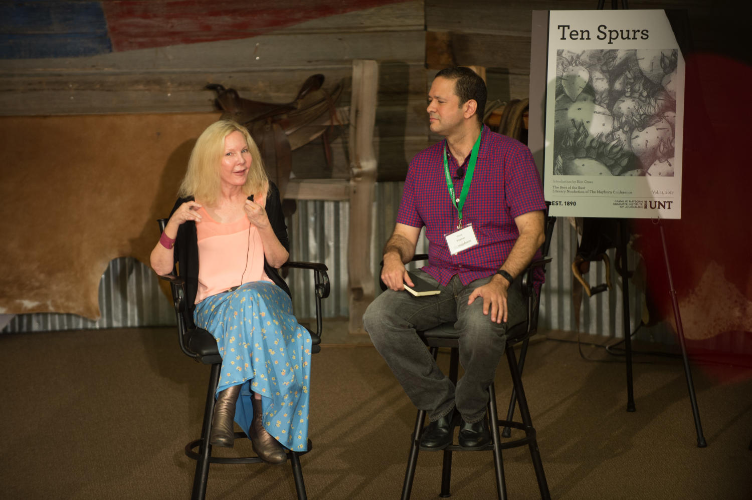 [Katherine Boo and Chris Vognar sitting on stage], Photograph of Katherine Boo and Chris Vognar sitting on stage in the Austin Ranch Banquet Hall. Boo is a keynote speaker for the Mayborn Literary Nonfiction Conference and Vognar is her moderator. To their side is the 2017 Ten Spurs anthology cover that was revealed earlier. Everything is taking place on the grounds of the Hilton DFW Lakes Executive Conference Center in Grapevine, TX.,