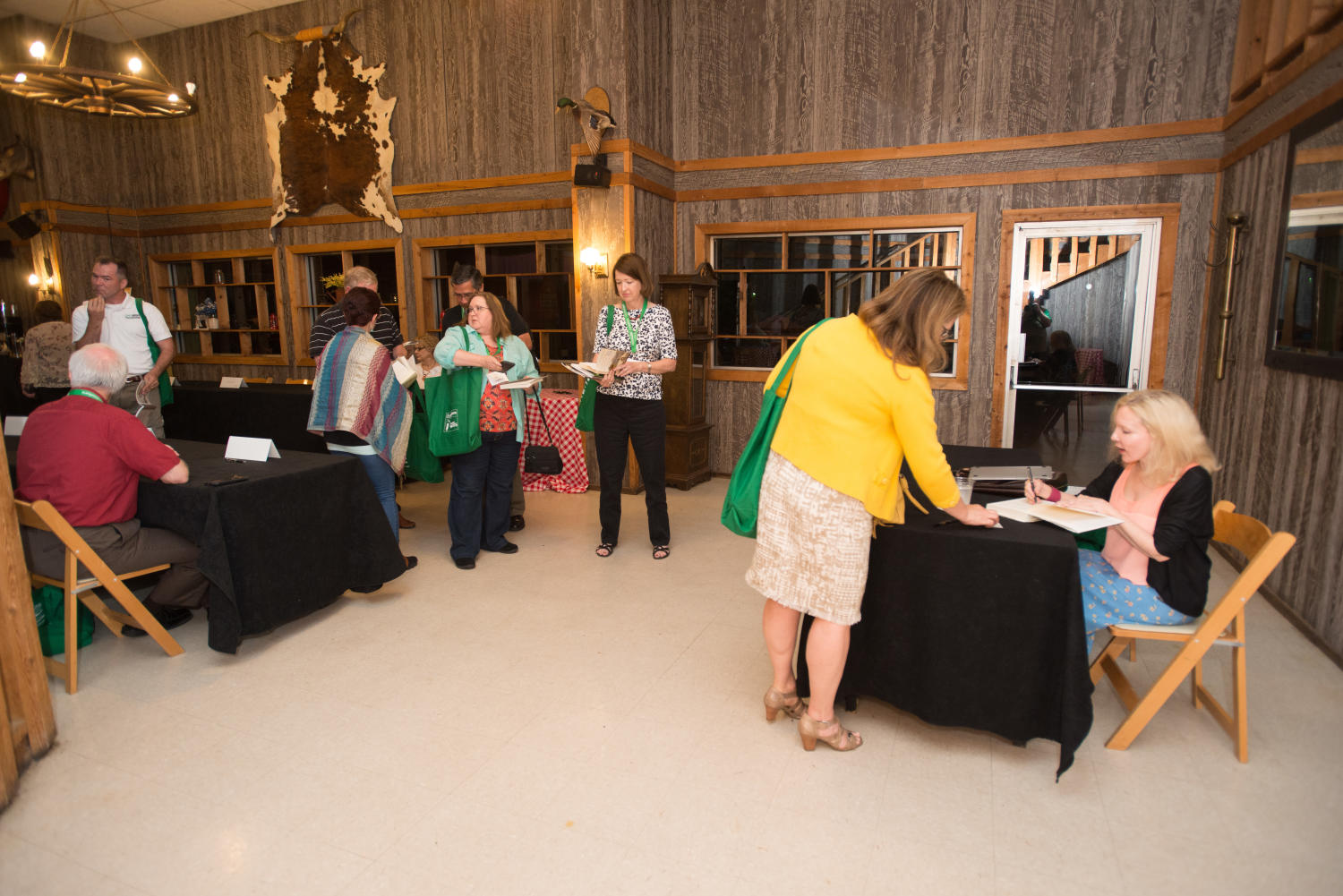 """[Book signings], Photograph of people having their books signed by the authors. Closest is Katherine Boo, author of """"Behind the Beautiful Forevers"""". The event was held during the Mayborn Literary Nonfiction Conference in the Austin Ranch Banquet Hall on the grounds of the Hilton DFW Lakes Executive Conference Center in Grapevine, TX.,"""