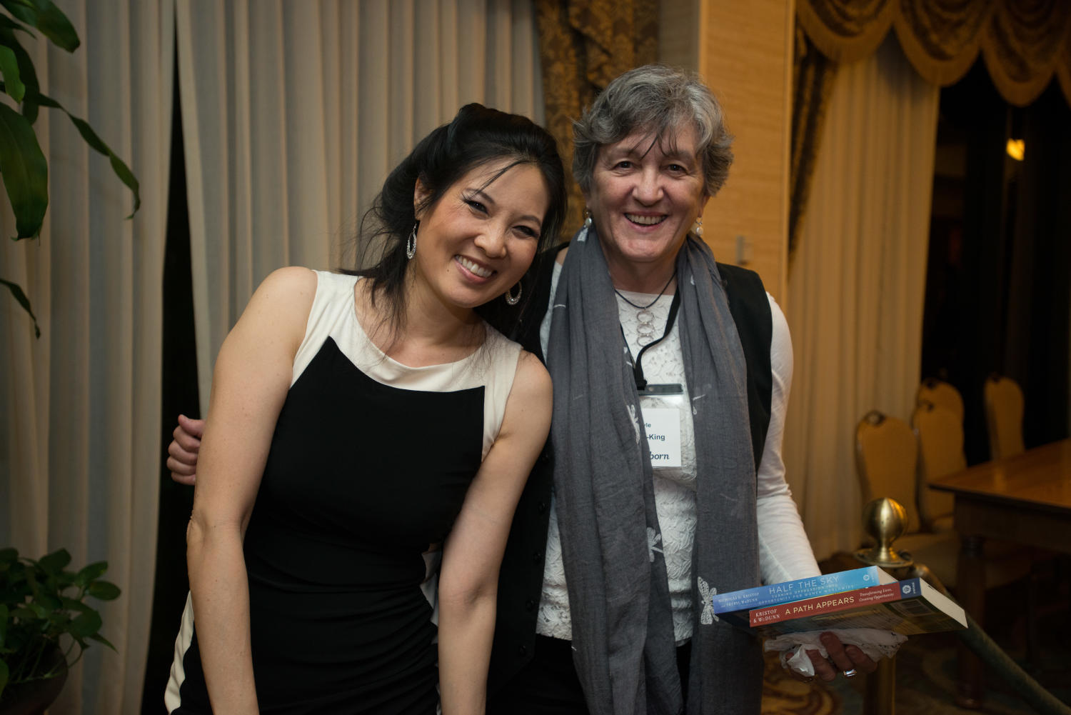 """[Sheryl WuDunn standing with a conference attendee], Photograph of Sheryl WuDunn (left) standing with a conference attendee who is holding copies of two of WuDunns books. A few letters of the womans name are visible on her name-tag, from the top """"-le"""" and then """"-King"""" in the section for last names. The book signing took place after the Literary Lights Dinner during the Mayborn Literary Nonfiction Conference. The conference was held at the Hilton DFW Lakes Executive Conference Center, Grapevine, TX.,"""