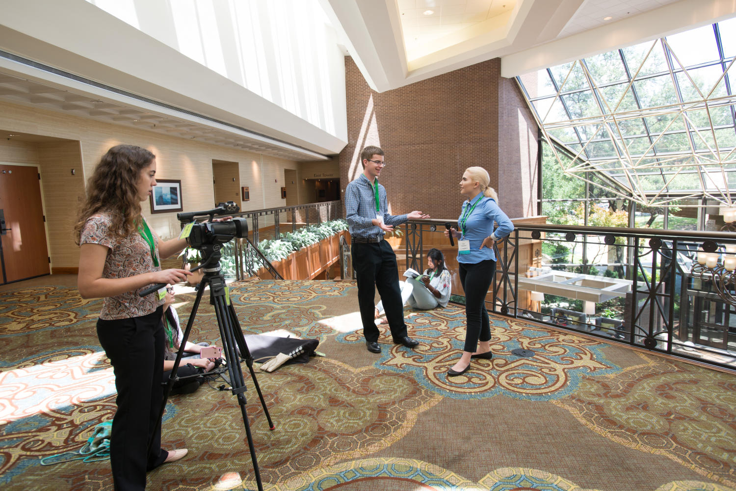 [Workshop participants recording videos], Photograph of the Multimedia High School Workshop participants utilizing new skills in the open areas of the Hilton DFW Lakes Executive Conference Center. Juliette Strope is using the camera on a tripod while Dylan Benson and Molly Chambers are recorded by the camera. Chamers is holding a microphone. Tanya Raghu and another student are sitting on the ground. The workshop took place during the Mayborn Literary Nonfiction Conference in Grapevine, TX.,