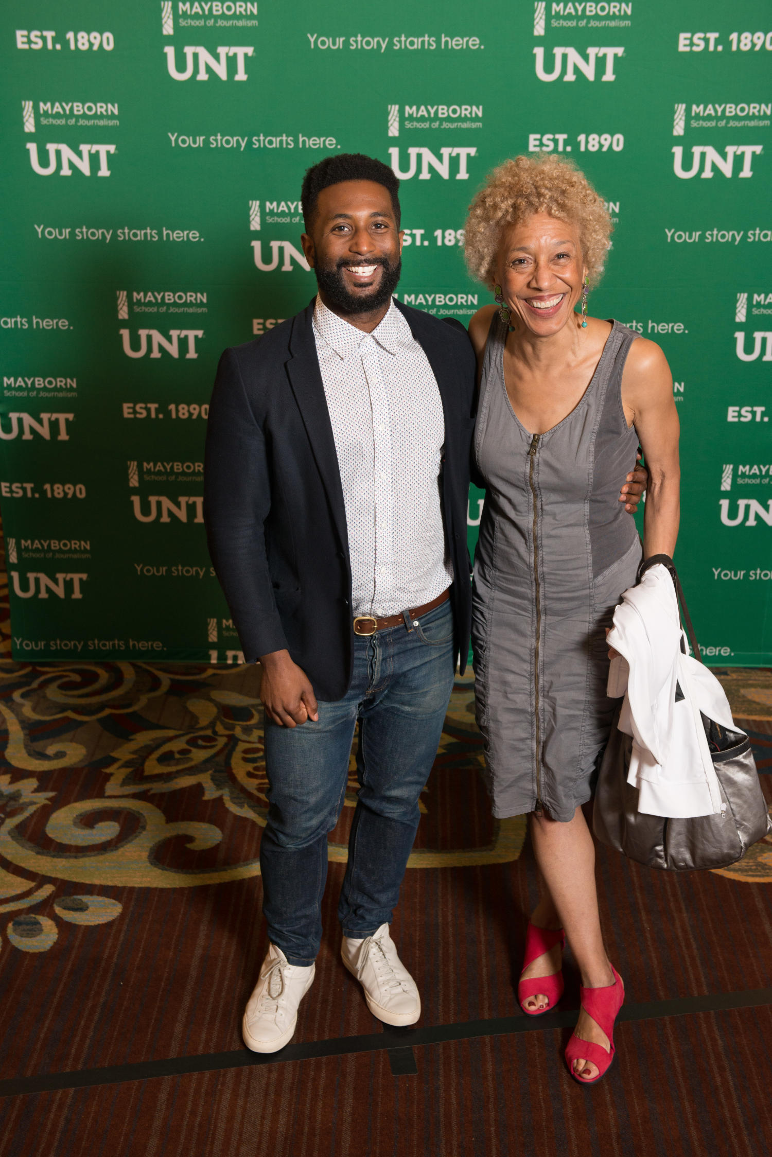 [Wesley Morris and Margo Jefferson standing together], Photograph of Wesley Morris and Margo Jefferson standing together in front of a Mayborn and UNT backdrop during the Literary Lights Dinner. The event was held as a part of the Mayborn Literary Nonfiction Conference in the International Ballroom at the Hilton DFW Lakes Executive Conference Center, Grapevine, TX.,