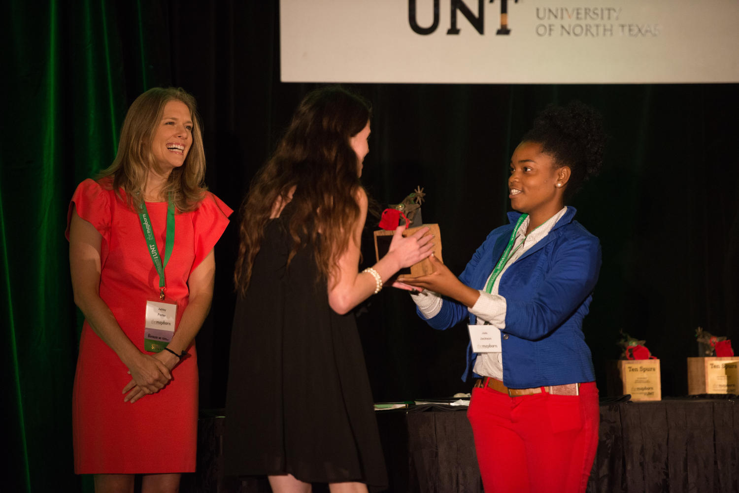 "[Meagan Flynn receiving Ten Spurs award], Photograph of Meagan Flynn, staff writer for the Houston Press, on stage while receiving Ten Spurs second place reported narrative award for her piece ""Life After Deportation"". Standing by the table is Ashley Porter. The awards ceremony took place during a dinner at the 2017 Mayborn Literary Nonfiction Conference, which was held at the Hilton DFW Lakes Executive Conference Center in Grapevine, TX.,"