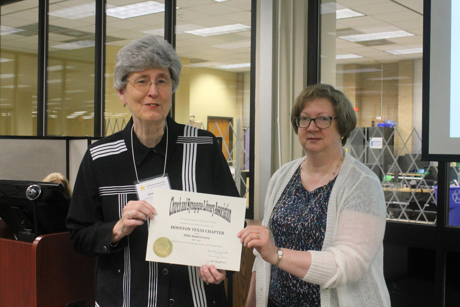 [Jane Hope accepting certificate for Houston Texas Chapter], Photograph of Jane Hope (left) accepting a certificate from Marcia Trauernicht (right). Trauernicht is congratulating the Houston Texas Chapter on their 30th anniversary which are being represented by Hope. The event took place during the 48th Church and Synagogue Library Association conference held at Willis Library at the University of North Texas in Denton, Texas.,