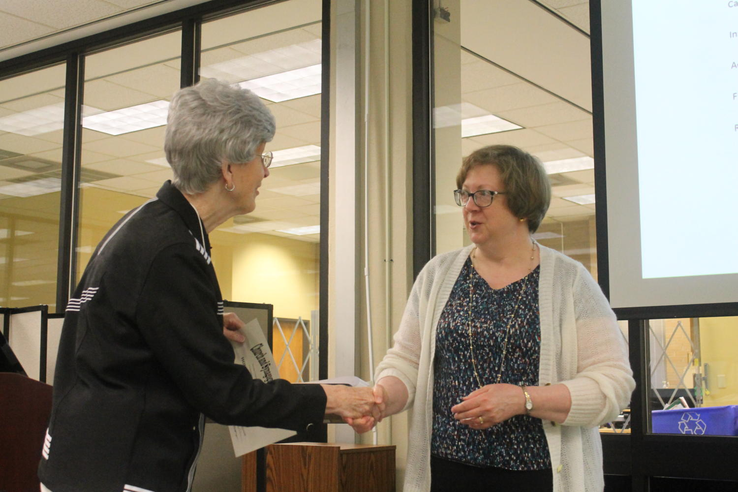 [Jane Hope shaking hands with Marcia Trauernicht], Photograph of Jane Hope (left) shaking hands with Marcia Trauernicht (right). Trauernicht is congratulating the Houston Texas Chapter on their 30th anniversary which are being represented by Hope as she accepted the certificate. The event took place during the 48th Church and Synagogue Library Association conference held at Willis Library at the University of North Texas in Denton, Texas.,