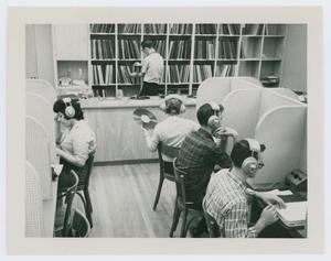 Black and white photograph of students sitting at partitioned desks with large headphones on. One student holds a record. The back wall of the room, behind the service desk, is filled with shelves of records.