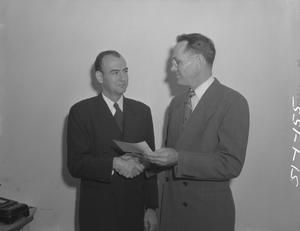 Primary view of object titled '[Two Men Shaking Hands and Holding a Paper Slip]'.
