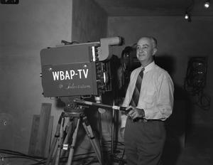 A man with white hair and wearing a suit and tie is seen standing behind a television camera.