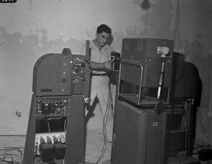Primary view of object titled '[Bogan in Control Room - Bogan with Movie Projectors]'.