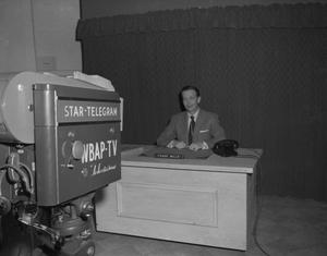 Primary view of object titled '[Frank Mills Sitting at a News Desk]'.