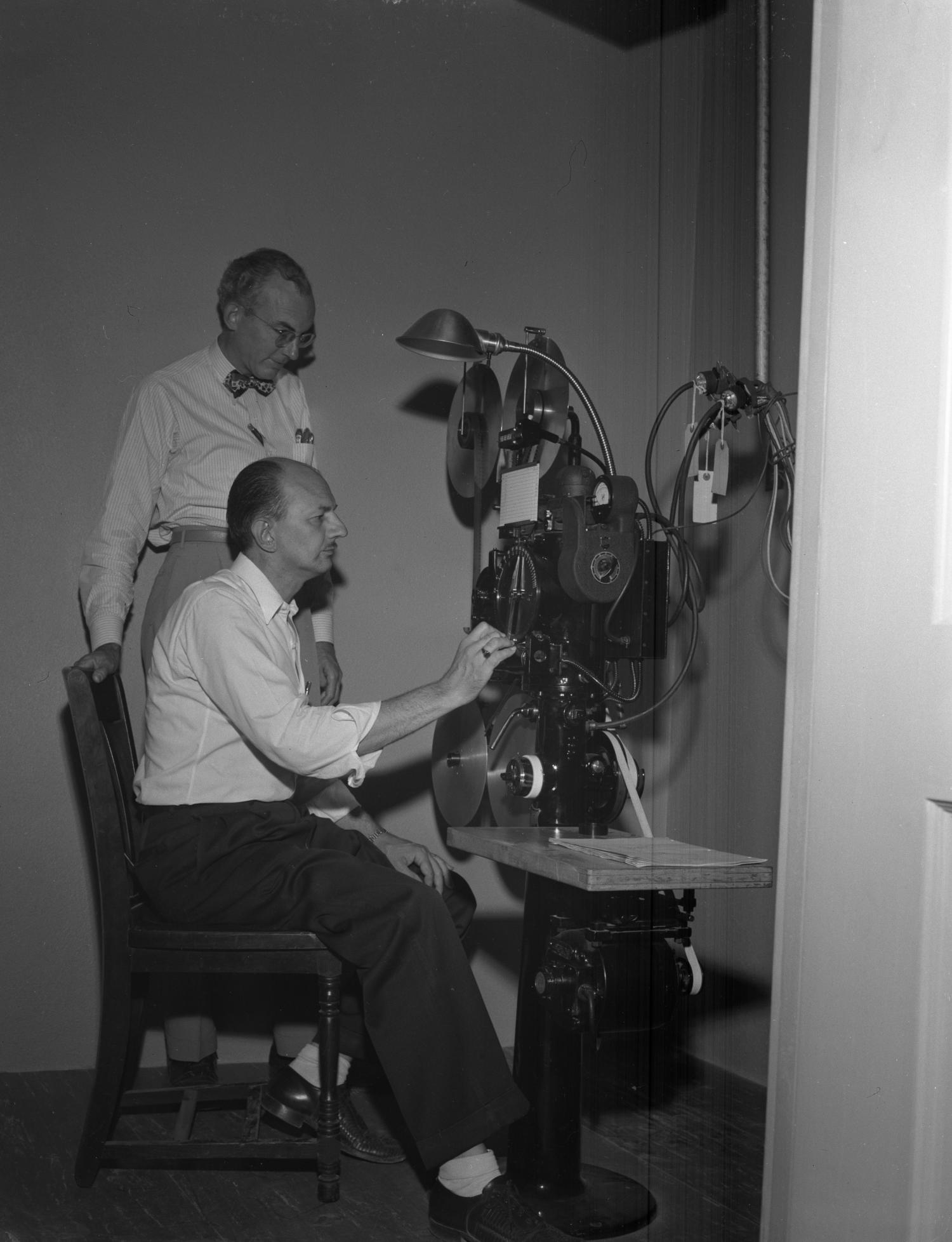 [Film Dept. - McClough and Saunders - Houston Mach and Printer], Photograph of two men examining film equipment.,