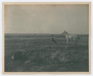 A black and white photo of a man and a horse. The horse is to the right of the man, and the man is to the left wearing a cowboy hat and is seen pulling away from the horse while holding on to the rope attached to it. They are in the middle of a field of grass.