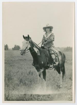 Old photo of a woman in a cowboy hat sitting on a black horse spotted with white. The woman is holding the reigns on the horse. They are in the middle of a field of grass.