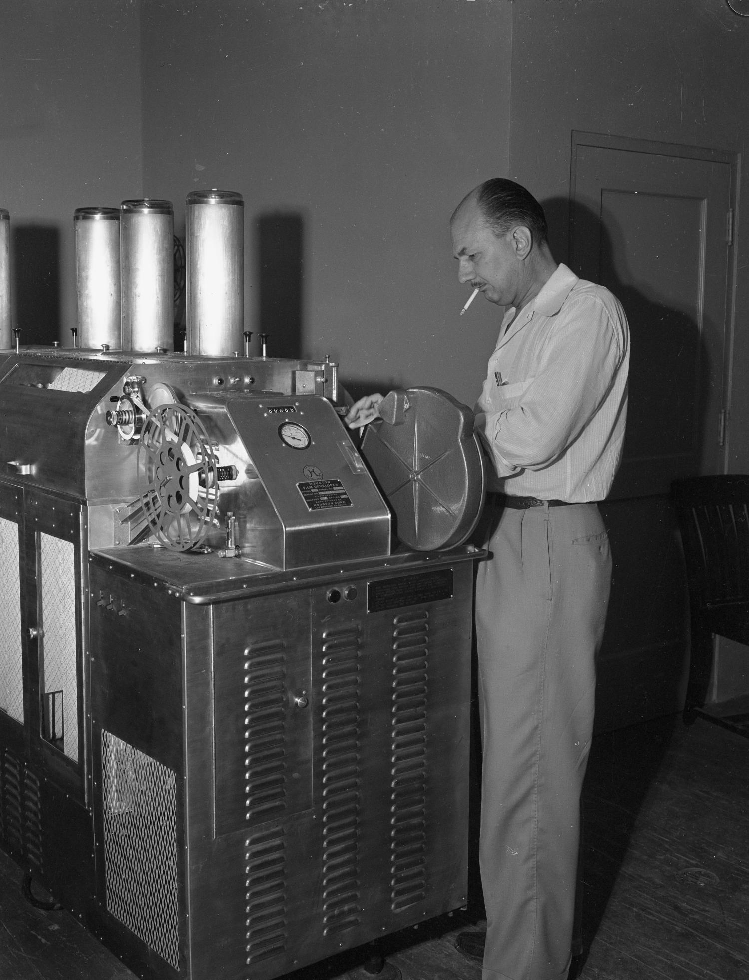 [Film-Dept.- McClough and Saunders - Houston Mach and Printer], Photograph of Houston Mach standing beside a printer.,