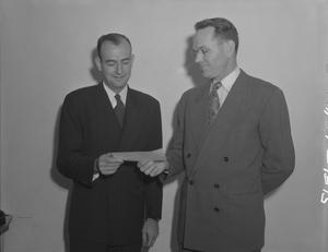 Primary view of object titled '[Two Men Holding a Paper Slip]'.