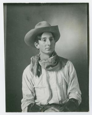 Photo of a man in a cowboy hat with a bandanna tied around his neck. He is wearing a white shirt, braces can be seen on his arms.