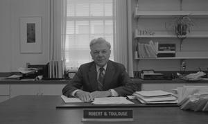 Primary view of object titled '[Dr. Robert Toulouse seated at his desk]'.