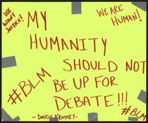 Yellow poster with duct tape around the edges. Red writing reads My humanity should not be up for depate, we want justice, we are human, #BLM.