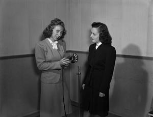 Primary view of [Jessie Sims and Jean Vance with a WBAP microphone]