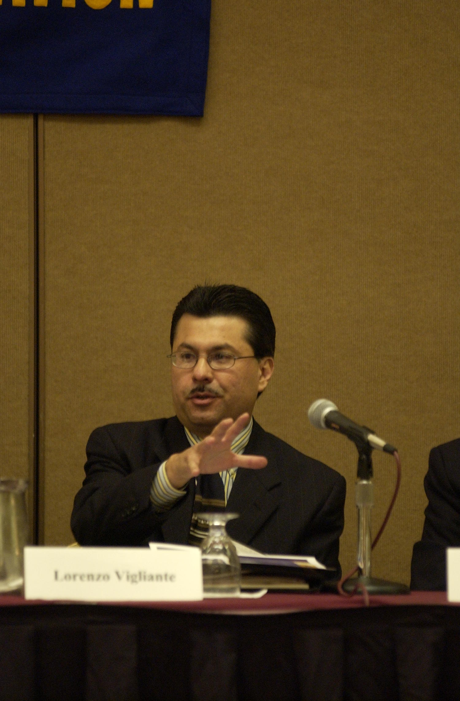 [Lorenzo Vigliante guest speaking at TDNA conference], Photograph of Lorenzo Vigliante in attendance at the 2004 Texas Daily News Association annual conference held in Corpus Christi. Vigliante is seen seated behind a table and in front of a microphone as he is a guest speaker at the conference.,