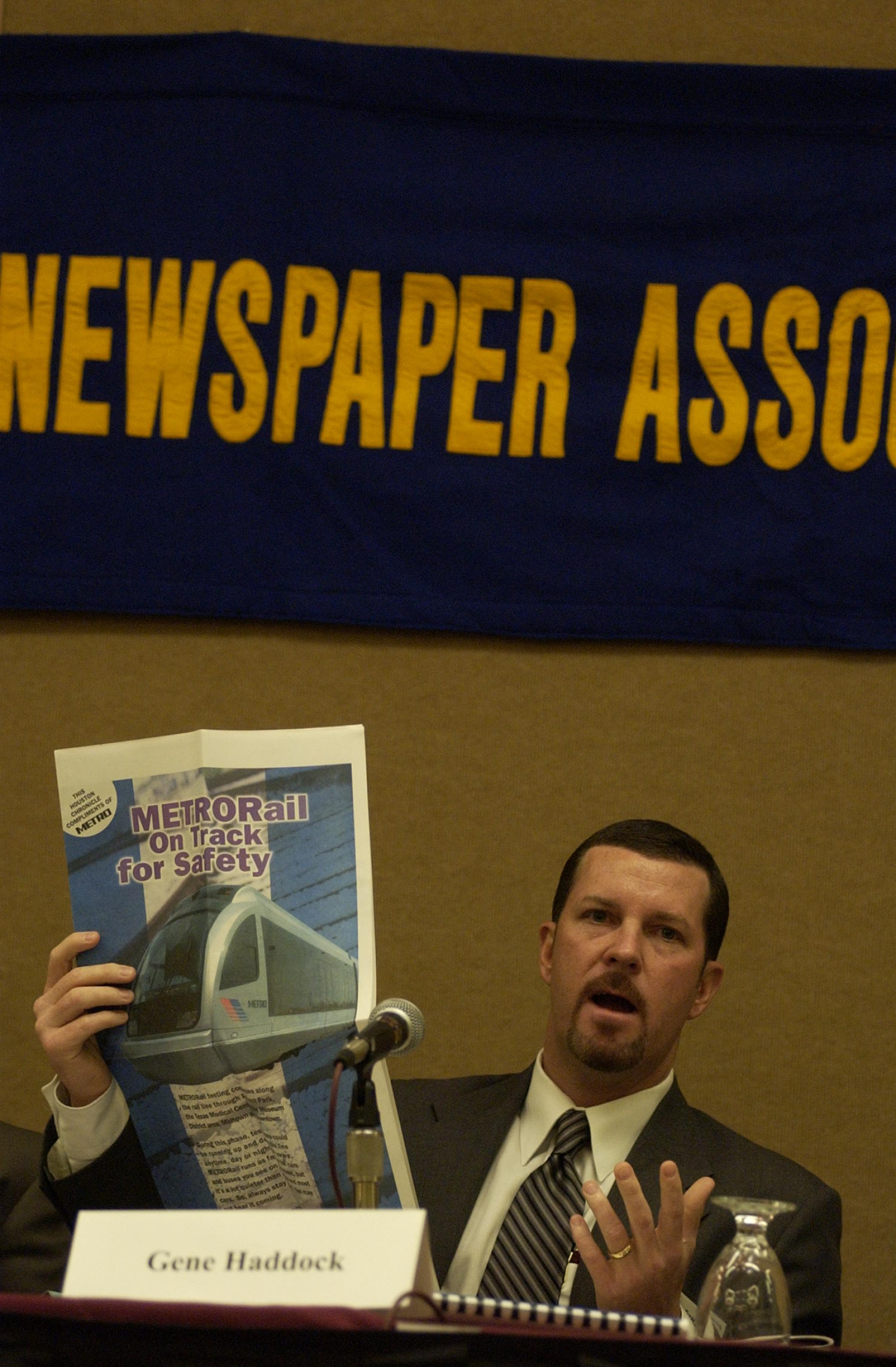 [Photograph of Gene Haddock], Photograph of Gene Haddock, a guest speaker attending the 2004 Texas Daily News Association annual conference held in Corpus Christi. Haddock is seen sitting behind a table and in front of a microphone and holding up a newspaper as he address the crowd during the conference.,