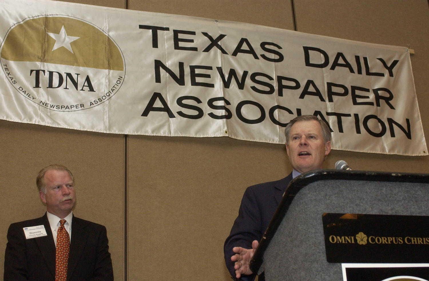 """[Wesley R. Turner speaking into microphone at TDNA conference, 2], Photograph of Wesley """"Wes"""" R. Turner seen speaking into a microphone during 2004 Texas Daily News Association annual conference held in Corpus Christi. Donnis Baggett is seen standing to the left of Turner and watching him as he addresses the conference crowd.,"""