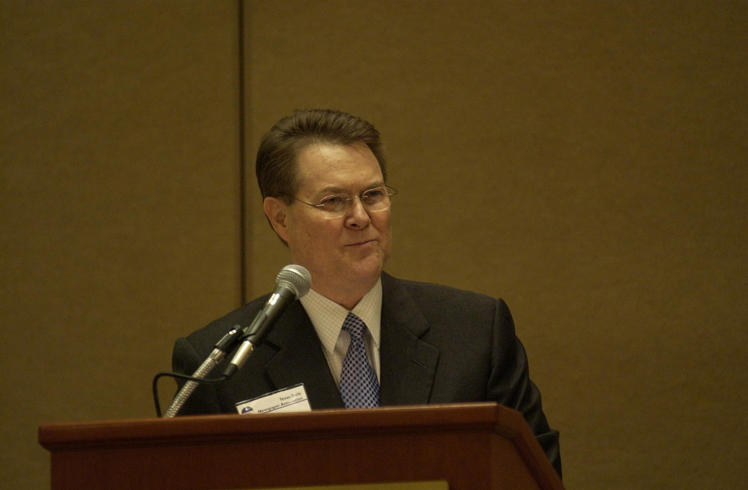 [Unidentified guest speaker at TDNA conference], Photograph of an unidentified guest speaker attending the 2004 Texas Daily News Association annual conference held in Corpus Christi. The guest is standing at a podium in the conference hall and talking into the microphone addressing the attendees.,