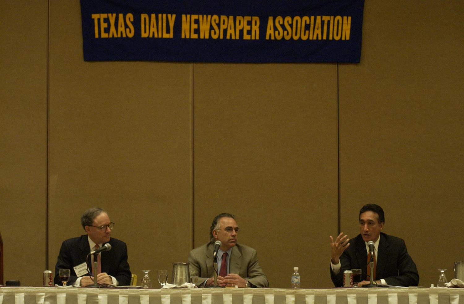 """[Guest speakers at TDNA conference], Photograph of Jeremy L. Halbreich (left) and two other unidentified guest speakers attending the 2004 Texas Daily News Association annual conference held in Corpus Christi. The guests speakers are seen sitting behind a table and speaking into their microphones and addressing the conference attendees. A banner above them reads """"Texas Daily Newspaper Association."""","""