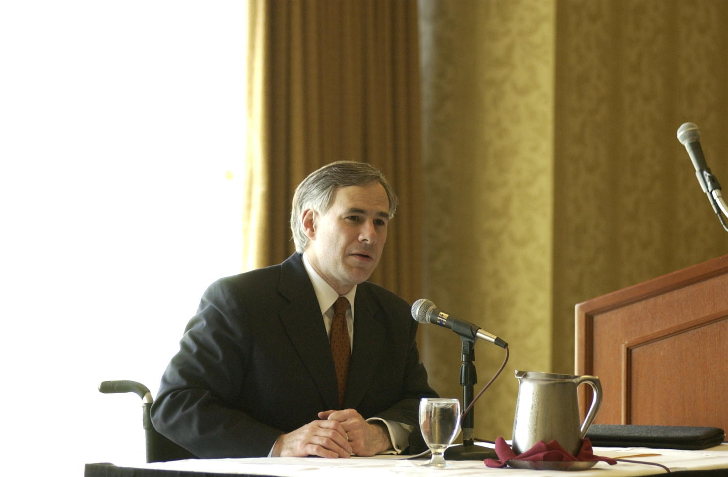[Unidentified man attending the TDNA conference, 4], Photograph of an unidentified man seated in a chair and attending the 2004 Texas Daily News Association annual conference held in Corpus Christi. The man is seen speaking into the microphone placed in front of him and addressing the conference attendees.,
