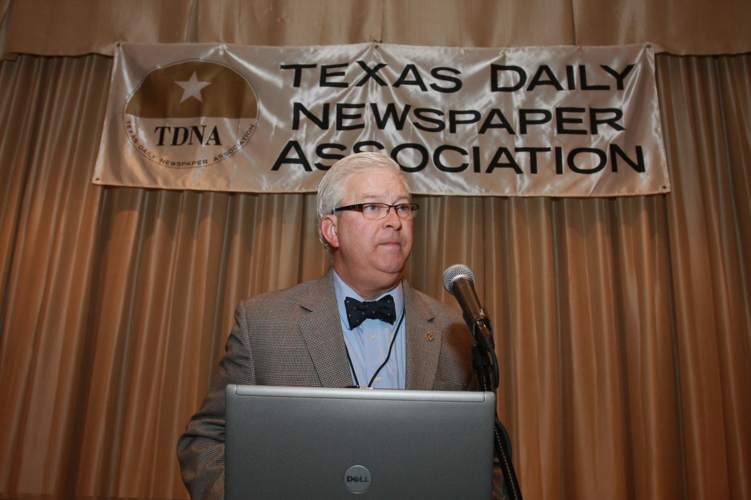 [Patrick Canty giving presentation at a TDNA conference], Photograph of Patrick Canty standing in front of a podium, with a laptop open before him, as he leans forward to speak into a microphone during the 2010 Texas Daily Newspaper Association annual meeting held in Houston, Texas.,
