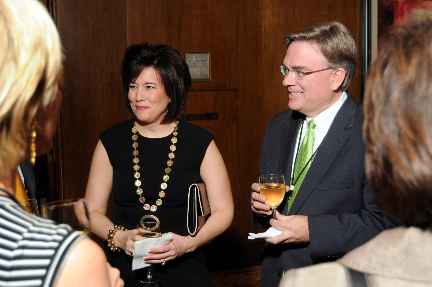 [Les Simpson and other guests at TDNA reception], Photograph of Les Simpson (center) and other unidentified guests conversing and drinking refreshments during a reception at the 2010 Texas Daily Newspaper Association annual meeting held in Houston, Texas.,