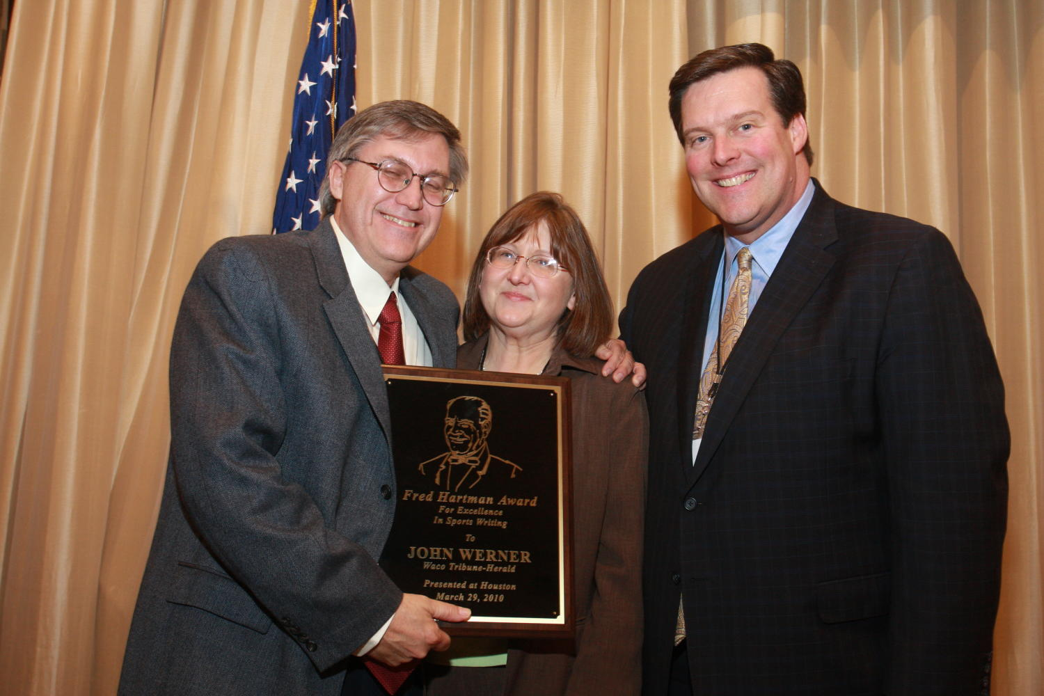 "[Nelson Clyde IV giving an award to John Werner], Photograph of Nelson Clyde IV (right) presenting an award to John Werner (left) and his wife, (center) at the 2010 Texas Daily Newspaper Association annual meeting held in Houston, Texas. The award reads, ""Fred Hartman Award for Excellence in Sports Writing to John Werner Waco Tribune-Herald presented at Houston, March 29, 2010."","